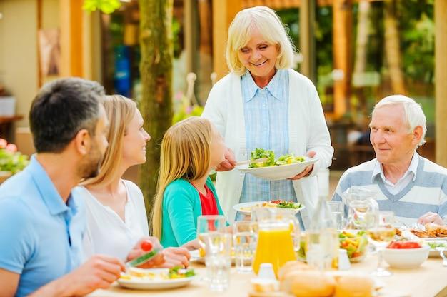 Familienzeit genießen. glückliche fünfköpfige familie, die gemeinsam am esstisch im freien sitzt