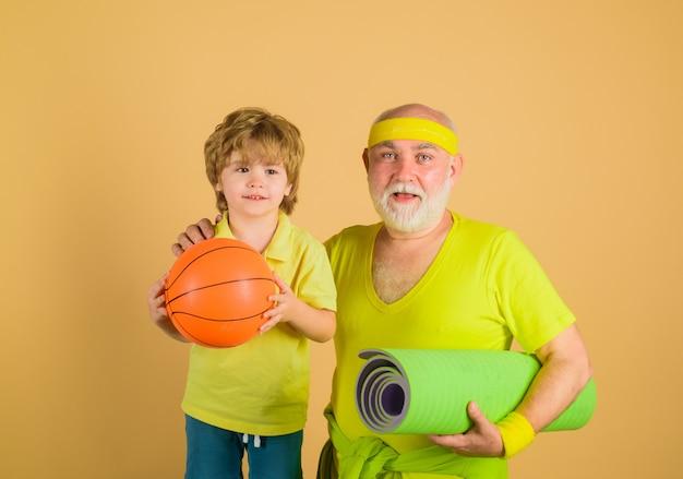 Familienzeit großvater und kind sportlicher familiensport daumen hoch alter mann mit yaga-teppich-porträt von