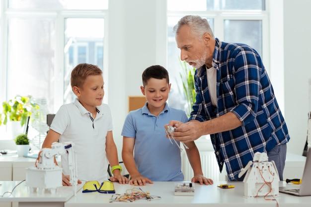 Familienzeit. netter angenehmer mann, der mit seinen enkelkindern spricht, während er ihnen roboter zeigt