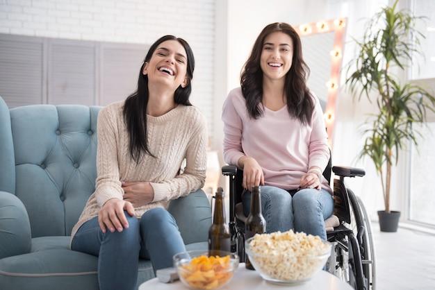Familienzeit. üppige schwester und behinderte frau, die film genießt und lacht Premium Fotos