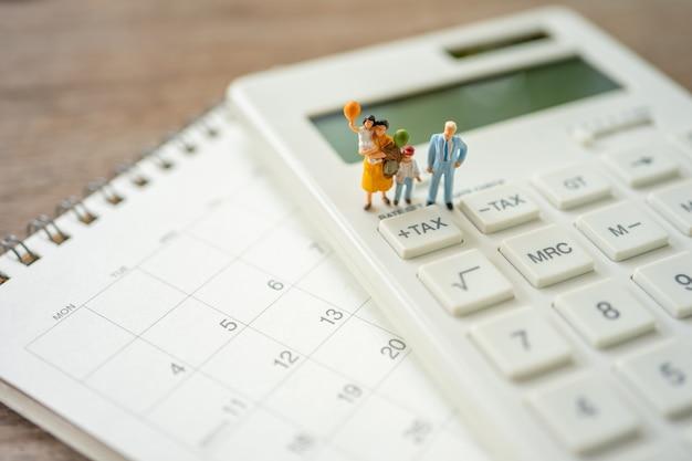 Family miniature people pay queue jährliches einkommen (tax) für das jahr auf dem taschenrechner.