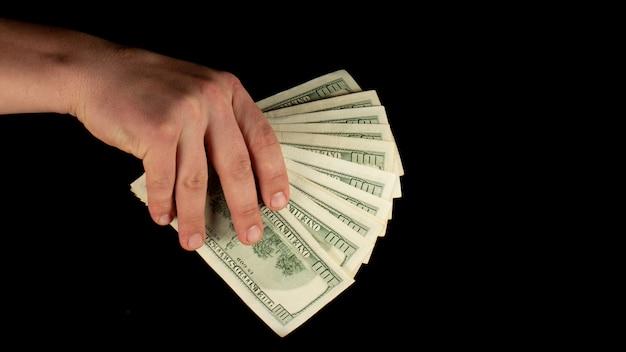 Fan von dollars in einer männlichen hand auf einem schwarzen hintergrund