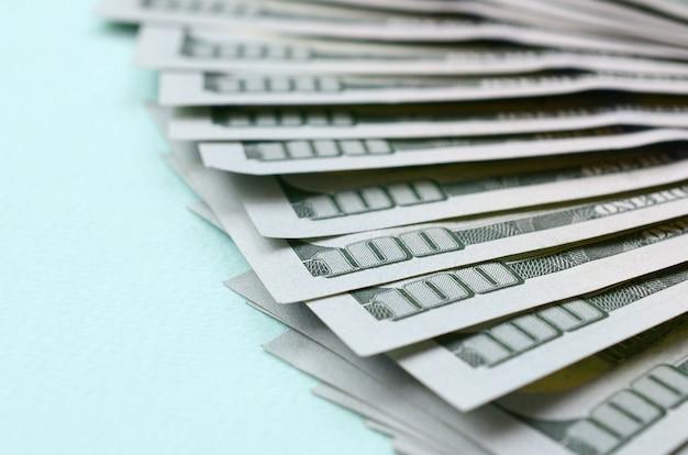 Fan von us-dollar rechnungen eines neuen designs liegt auf einem hellblauen hintergrund