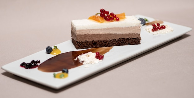 Fancy triple-mousse-schokoladennachtisch, verziert mit waldfrüchten und schokoladensauce