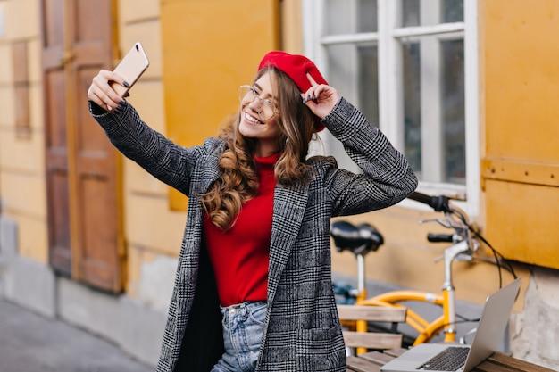 Fangen frau mit lockiger frisur unter verwendung des smartphones, während selfie nahe haus machen