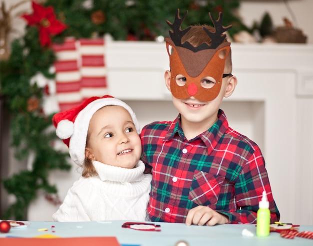 Fanny kinder mädchen und junge in santa mütze und hirschmaske gratulieren einander frohe weihnachten und ein gutes neues jahr und umarmen sich.
