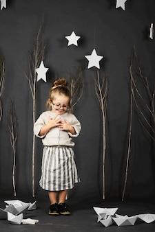 Fanny kleines mädchen mit brille auf grauem hintergrund mit sternen, bäumen und papierbooten