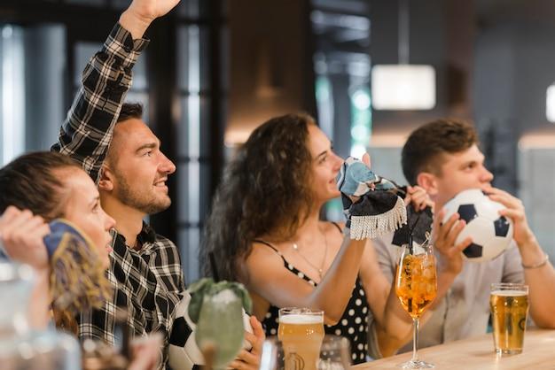 Fans beobachten fußballspiel im fernsehen in der bar