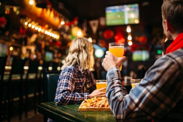 Fans schauen sich das match an und trinken bier in der sportbar