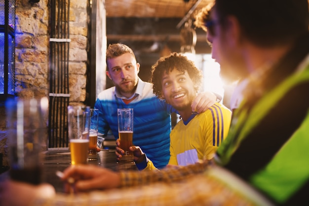Fans verschiedener fußballvereine diskutieren freundlich darüber, wessen team in einem örtlichen pub besser ist.