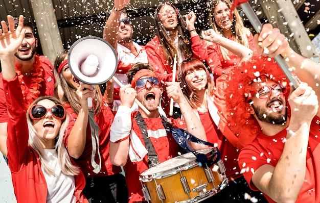 Fans von fußballfans, die beim internationalen fußballspiel mit konfetti jubeln - niederländische winkelkomposition