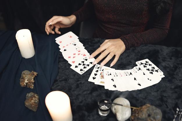 Fantasie schönes zigeunermädchen. wahrsagerin, die zukunft auf magischen tarotkarten liest.