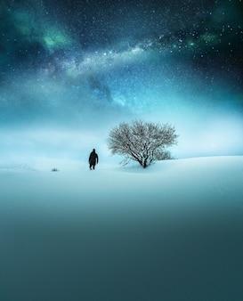 Fantasiekonzept eines in schwarz gekleideten reisenden, der im schnee mit atemberaubendem sternenhimmel erforscht