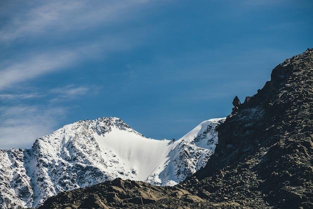 Fantastische alpenlandschaft mit dunklen rockies und hohen schneebedeckten bergen bei sonnenschein unter blauem himmel mit cirruswolken. schöne hochlandlandschaft mit scharfen schwarzen felsen und berggipfel mit schnee.