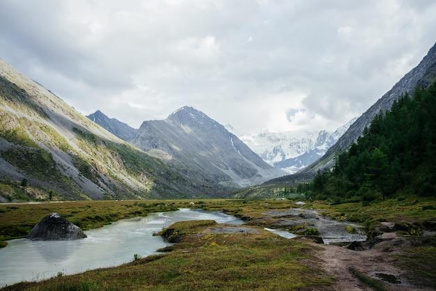 Fantastische alpine aussicht auf bergsee und große gletscher unter düsterem himmel. dunkle atmosphärische hochlandlandschaft mit hohen schneebedeckten bergen und großen felsen. wunderbare berglandschaft bei bewölktem wetter.