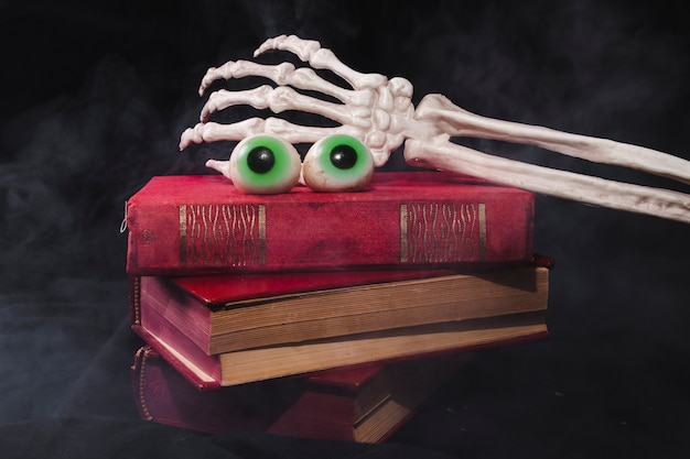 Fantastische augen mit der skeleton hand mit stapel des buches
