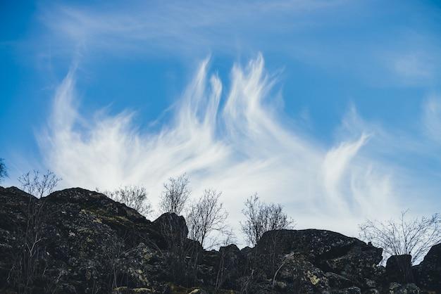 Fantastische berglandschaft mit schönen cirruswolken am blauen himmel über silhouetten von großen steinen und bäumen. ungewöhnliche schleuderwolken über einem hohen dunklen hügel aus großen felsbrocken mit moosen und flechten.