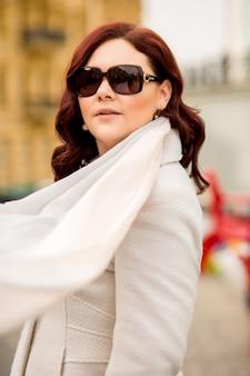 Fantastische erwachsene dame mit trendigem mantel und schal, die mit sonnenbrille auf der straße posiert