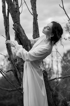 Fantastische feenhafte schöne frau im weißen langen kleid auf altem trockenem baum. mädchenprinzessin im sumpf. mode-modell sexy mädchen posiert auf einem baum am see. märchen
