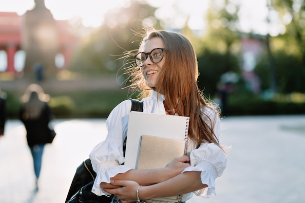 Fantastische glückliche junge studentin zurück zum college mit notizbüchern und laptop, zur universität mit glücklichem lächeln auf sonniger straße gehend