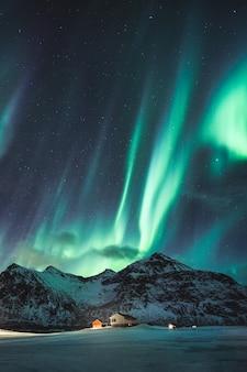 Fantastische grüne aurora borealis, nordlichter mit sternen, die auf schneebedeckten bergen am nachthimmel im winter auf den lofoten-inseln, norwegen leuchten
