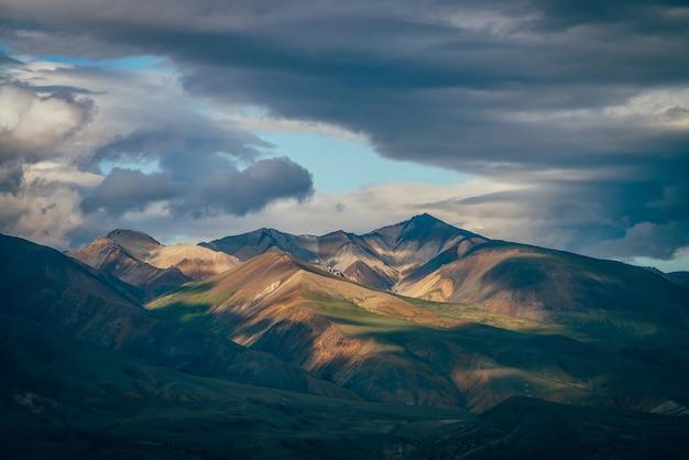 Fantastische hochlandlandschaft mit großen bergen und blauer freigabe im bewölkten himmel bei bewölktem wetter. blaues oberlicht im bewölkten himmel über riesigen mehrfarbigen bergen im sonnenlicht. bunte berglandschaft