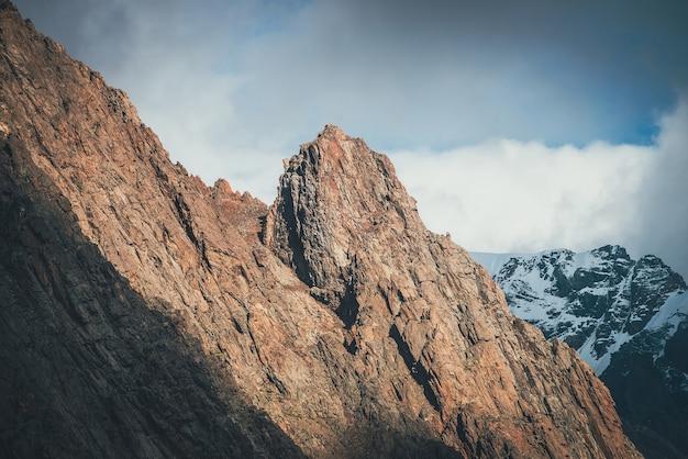 Fantastische landschaft mit sonnenbeschienenem felsgipfel auf dem hintergrund hoher schneebedeckter berge in niedrigen wolken. atmosphärische alpenlandschaft mit scharfen felsen und riesigen schneebedeckten bergen bei bewölktem himmel. malerischer alpenblick.