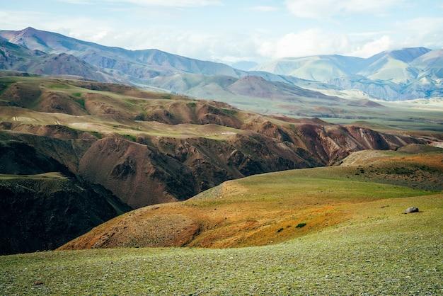Fantastische lebendige berglandschaft mit tiefer schlucht. mehrfarbige berge, grüner pass und schlucht im sonnenlicht. malerische sonnige landschaft mit schönen hügeln und felsen. bunter blick auf ungewöhnliches relief.