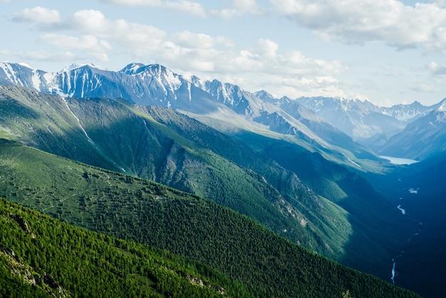 Fantastische luftaufnahme zu großen bergen, gletscher und grünem waldtal mit alpensee und fluss.