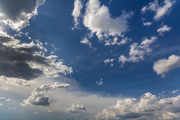 Fantastische panoramaansicht der hellen weißen geschwollenen wolken, die von der sonne beleuchtet werden, die sich gegen tiefblauen sommerhimmel ausbreitet, der sich mit wind bewegt. schönheit und kraft der natur, meteorologie und klimawandel.