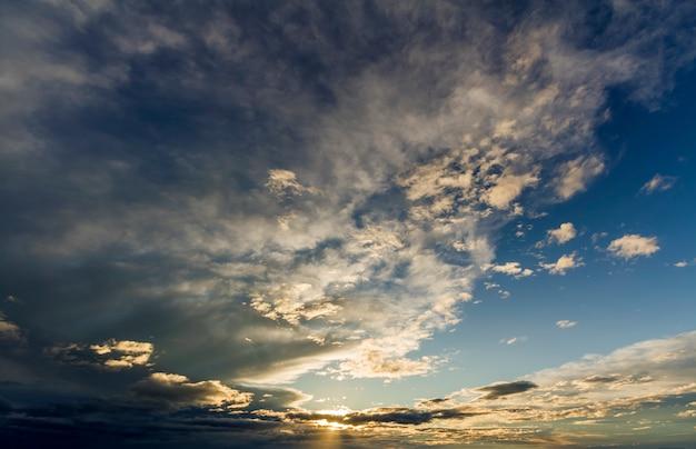 Fantastische panoramaansicht der hellen weißen grauen dunklen breiten geschwollenen wolken, die durch die sonne beleuchtet werden, die sich gegen tiefblauen himmel ausbreitet, der sich mit wind bewegt. schönheit und kraft der natur, meteorologie und klimawandel.