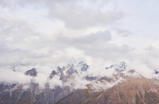 Fantastische schneebedeckte berge in den wunderschönen cumuluswolken. hauptkaukasischer kamm. typ mount ushba meyer, georgia