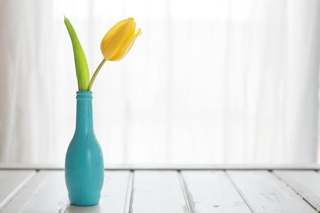 Fantastische szene mit blauer vase und tulipan