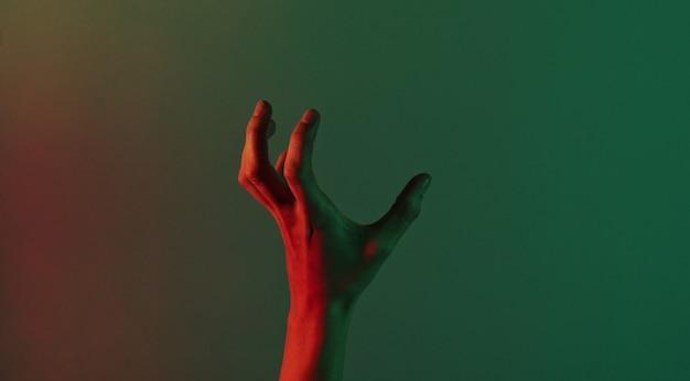 Fantastische weibliche hand mit blauem neonrotem grünem licht