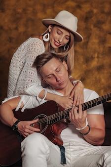 Fantastischer junger mann und frau in weißer kleidung mit gitarre im innenraum des wohnzimmers. paar auf sofa mit gitarre. konzept des lernens zu hause oder des musizierens zu hause und der musikausbildung. platz kopieren