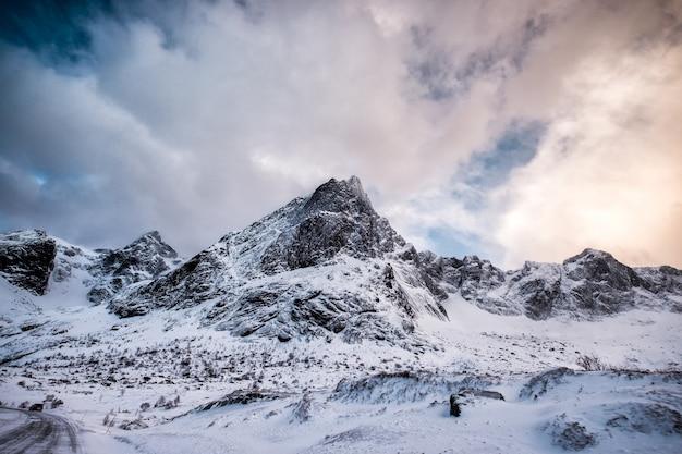 Fantastischer schneebedeckter gebirgszug mit bewölktem himmel