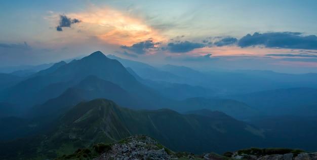 Fantastischer sonnenaufgang oder sonnenuntergang über grünem bergrücken bedeckt mit dichtem blauem nebel. helle orange sonne, die im weichen bewölkten himmel über entferntem horizont aufsteigt. schönheit der natur, tourismus und reisekonzept.