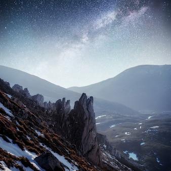 Fantastischer sternenhimmel. herbstlandschaft und schneebedeckte gipfel. karpaten, ukraine europa