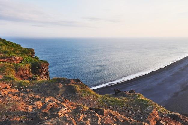 Fantastischer strand in südisland, schwarze sandlava. der malerische sonnenuntergang