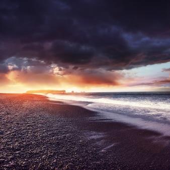 Fantastischer strand in südisland, schwarze sandlava
