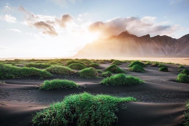 Fantastischer westen der berge und der vulkanischen lavasanddünen auf dem strand stokksness, island. bunter sommermorgen island, europa