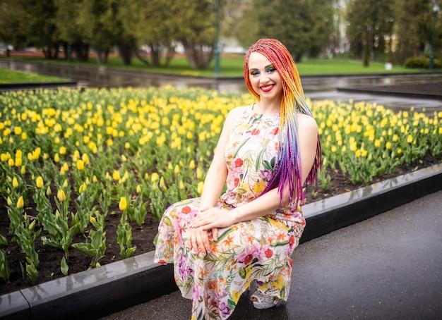 Fantastisches mädchen mit regenbogenzöpfen und ausdrucksstarkem glitzer-make-up. sie sitzt und genießt das warme frühlingswetter in einem grünen park mit großen tulpenbeeten.