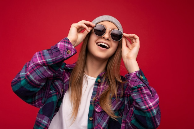 Fantastisches nahaufnahmefoto einer erstaunlich schönen, glücklichen jungen dunkelblonden frau, die auf rotem hintergrund isoliert ist und ein farbenfrohes, stylisches hemd mit grauem hut und einer modernen sonnenbrille trägt, die nach oben schaut und spaß hat