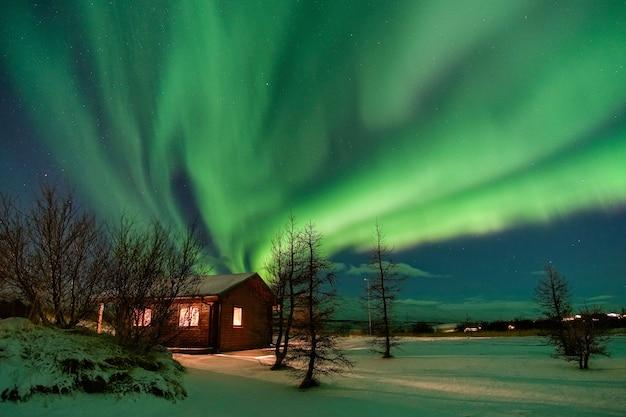 Fantastisches nordlicht über einem schönen häuschen, das vom schnee bedeckt wird