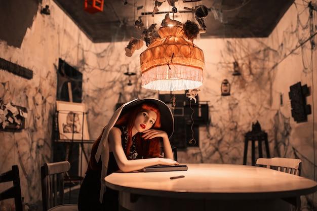 Fantastisches rothaariges mädchen im schwarzen retro-kleid sitzen am tisch. schöne vintage frau. fantastische dame im retro-hut. vintage schriftsteller sitzen im innenraum. schlanke frau mit roten haaren. der schriftsteller schreibt ein buch. tischlampe