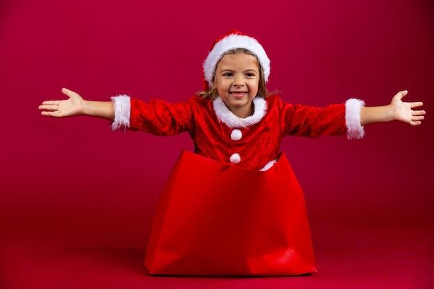 Fantastisches, sehr glückliches kaukasisches mädchen entkommen aus der roten geschenkpackung. mit offenen händen überraschen. frohes neues jahr. rote wand.