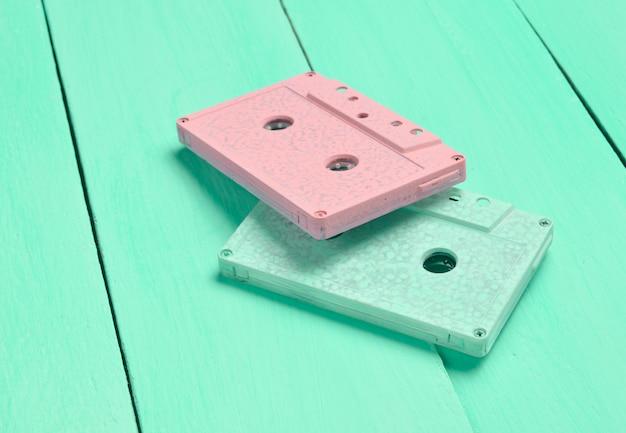 Farb-audiokassetten auf einem pastellfarbenen hölzernen hintergrund. retro-audio-technologie. trend des minimalismus.