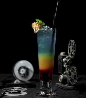Farbalkoholcocktail mit blume und schwarzem rohr.