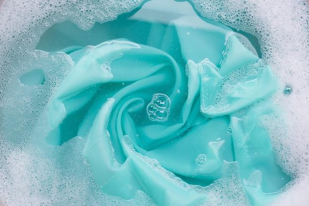 Farbe kleidung in pulverreiniger wasserlösung einweichen. wäschereikonzept