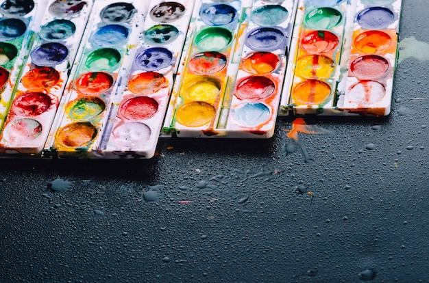Farbe lag auf der schwarzen oberfläche, hübscher lichthintergrund, kreativität